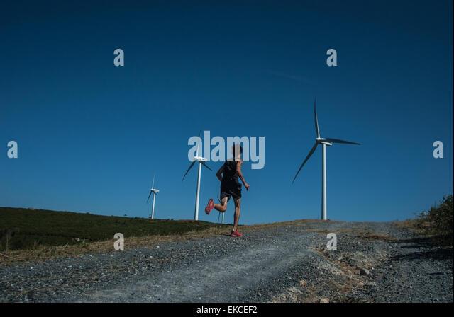 Mitte erwachsener Mann Joggen auf der Straße Windkraftanlagen Sie in Ferne Stockbild