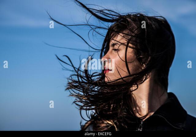 Junge Frau, die seitlich mit Haaren im wind Stockbild