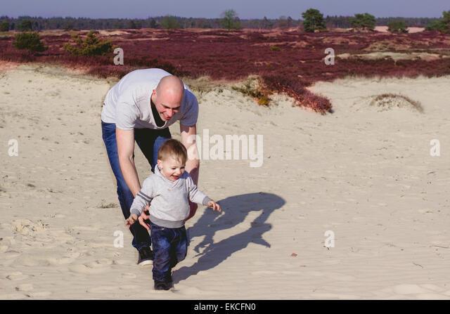 Vater und Sohn spielen am Strand Stockbild