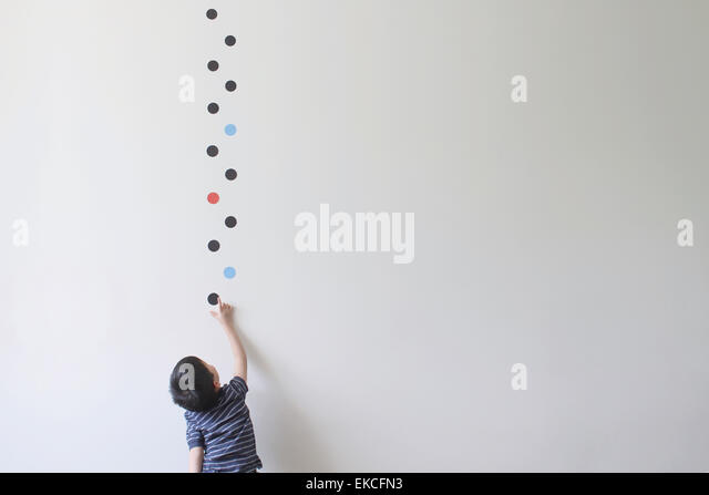 Junge, die versuchen, eines der Dot-Muster von der Wand zu holen Stockbild
