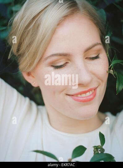 Eine hübsche Frau lächelnd mit den Augen geschlossen. Stockbild