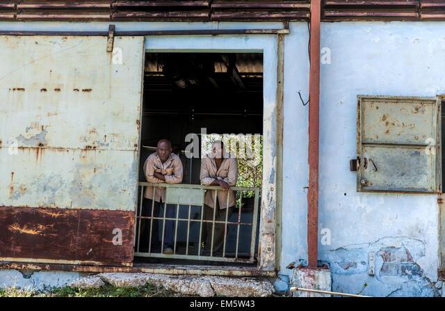 Zwei kubanische Männer mit Blick auf einen vorbeifahrenden Zug in einem abgelegenen Teil von Kuba. Die Gebäude Stockbild