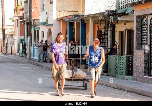 Zwei kubanische Männer ziehen einen Wagen in einer Straße in der abgelegenen Teil von Kuba Stockbild