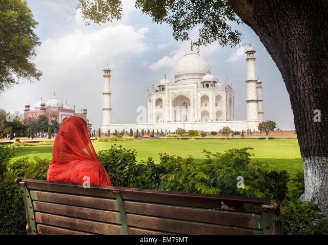 Frau im roten Schal auf der Bank im Schatten sitzen und mit Blick auf das Taj Mahal in Agra, Uttar Pradesh, Indien Stockbild