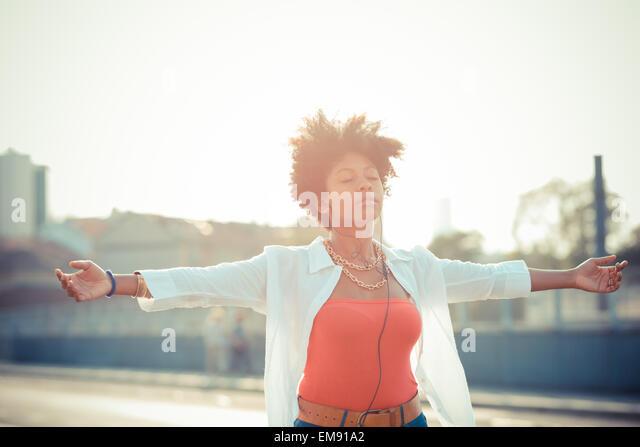 Junge Frau mit offenen Armen in Stadt Smartphone Musik tanzen Stockbild