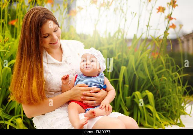 Cute smiling Baby Kleinkind auf Mamas Knie sitzen und Spaß haben. Entspannen im grünen Sommer Park. Selektiven Stockbild