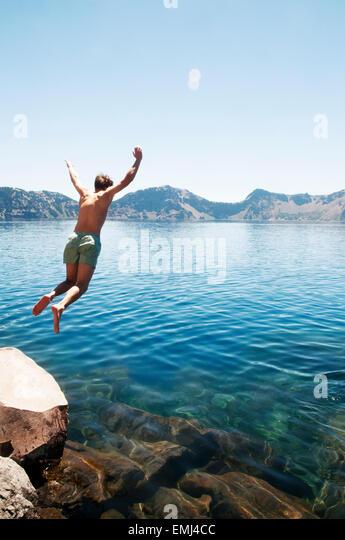 Junger Mann in See springen Stockbild