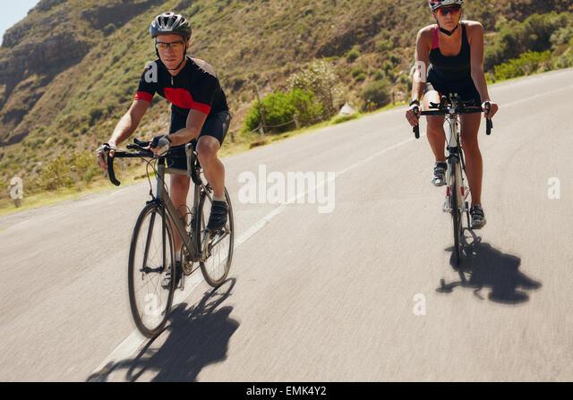 Zwei Athleten bergab auf Rennrädern. Mann und Frau Radfahrer fahren auf der Landstraße. Triathlon-Training. Stockbild