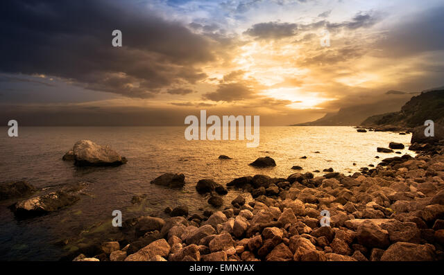 Sonnenuntergang über Felsen am Meer Stockbild