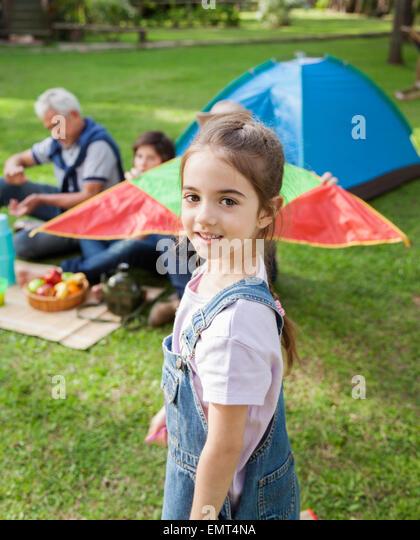 Lächelnde Mädchen stehen auf Campingplatz Stockbild
