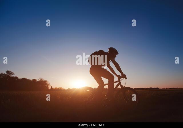 Silhouette der junge Mann auf dem Fahrrad bei Sonnenuntergang Stockbild