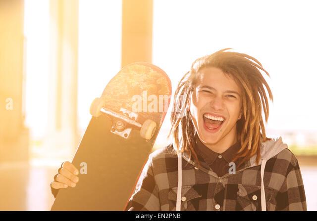 Porträt des jungen Kerl mit Skateboard und Rasta Haar in ein Lifestyle-Konzept warm Filter angewendet Stockbild