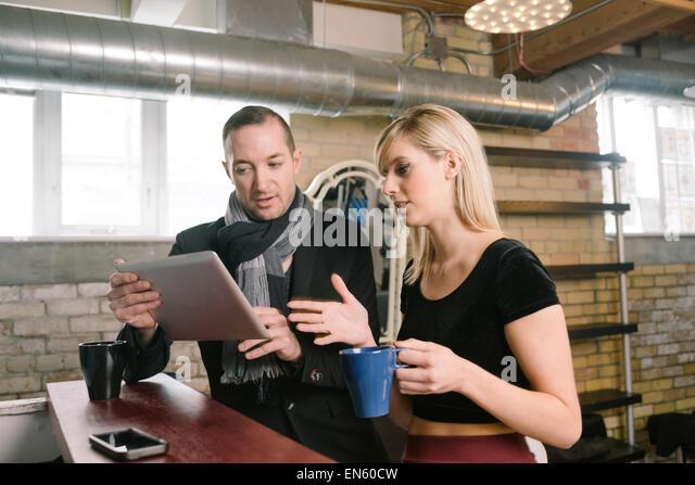Unternehmer-Ehepaar diskutieren Geschäft in ihrem Büro auf Laptop-computer Stockbild