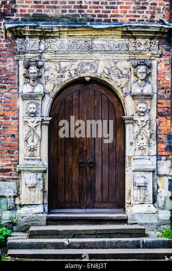 Mittelalterliche rundbogige Tür, dunklen hölzernen Doppeltüren, aufwendige verschönert Surround, Stockbild