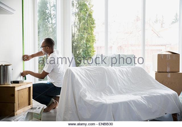 Mann, die Wohnzimmerwand Maler Klebeband zuweisen Stockbild