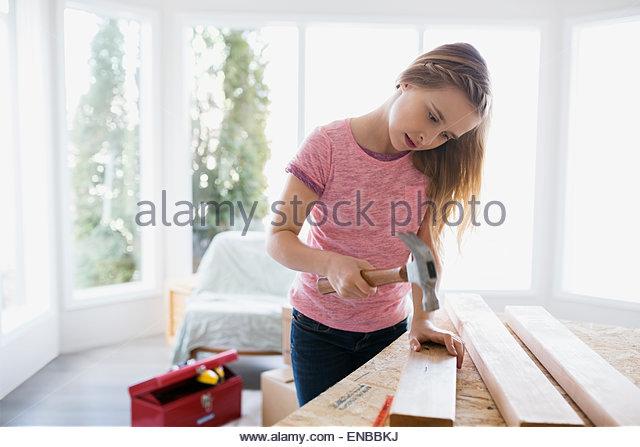 Blonde Mädchen Hämmern Nagel ins Holz trim Stockbild