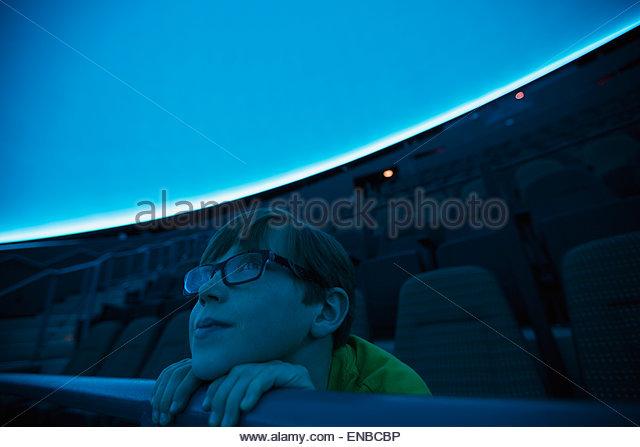 Neugieriger Junge genießen Planetariumsshow Stockbild