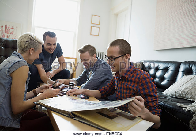 Freunden auf der Suche im Fotoalbum im Wohnzimmer Stockbild
