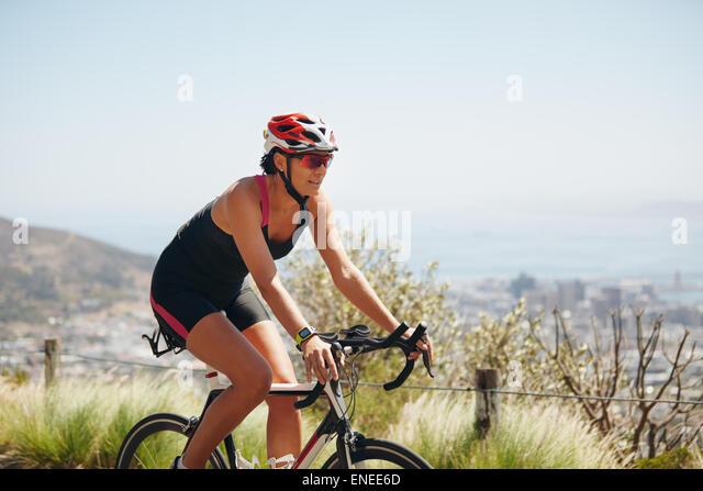 Im Freien Schuss von einem weiblichen Radfahrer fahren Rennrad. Frau Radfahren Landschaft unterwegs. Training für Stockbild