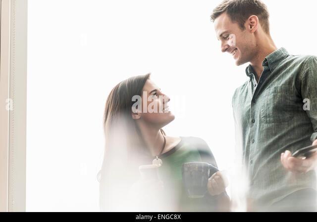 Ein Mann und eine Frau im Gespräch bei einem Kaffee in einem Büro. Stockbild