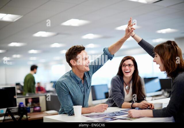 Drei Menschen in einem Büro mit Blick auf Fotografien und eine hohe fünf Geste. Stockbild