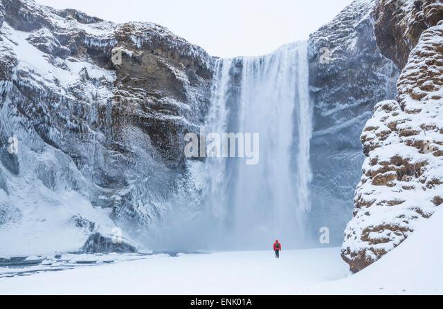 Eine Person im roten Jacke Wandern im Schnee in Richtung Skogafoss Wasserfall im Winter, Skogar, South Island, Island Stockbild