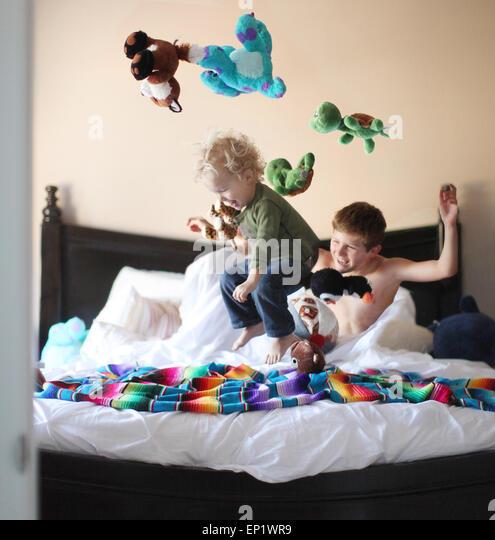Junge auf Brüder Bett springen und werfen Stofftiere in der Luft Stockbild