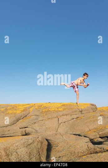 Jungen stehen auf einem Bein auf einem Felsen Stockbild