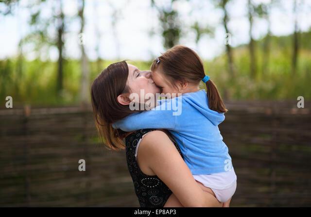 Die Liebe einer Mutter. Mama hält kleine Tochter in die Arme und küßt sie auf die Stirn. Selektiv Stockbild