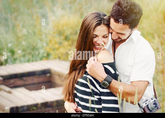 romantisches Brautpaar in Liebe und Spaß mit Daisy am See im Freien im Sommertag, Schönheit der Natur, Stockbild