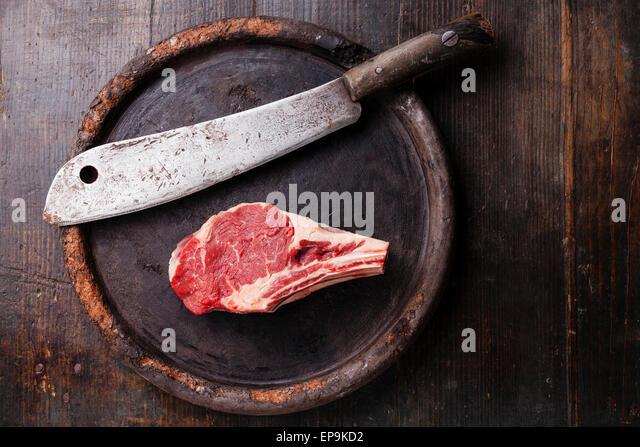 Rohes Fleisch Ribeye Steak Entrecote und Fleischerbeil auf dunklem Hintergrund Stockbild