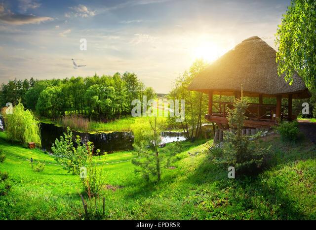 Hölzerne Laube mit Reetdach nahe Fluss Stockbild