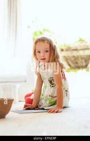 Porträt der niedliche kleine Mädchen sitzend auf Stock zu Hause zeichnen Blick in die Kamera. Grundschulkind Stockbild
