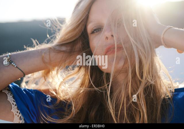 Frau rennt ihren Händen durch ihr Haar Stockbild