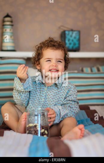 Lächelndes Mädchen sitzt auf dem Bett Süßigkeiten essen Stockbild