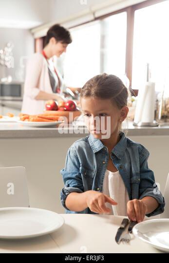 Mädchen, die Tischdecken, Mutter, die Zubereitung von Speisen im Hintergrund Stockbild
