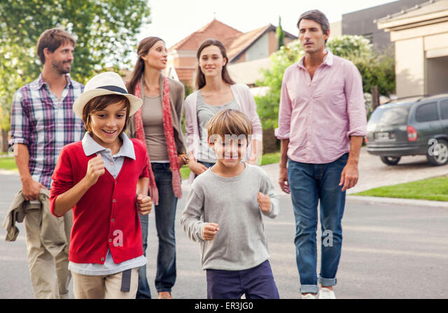 Familie gehen zusammen durch Vorort Stockbild