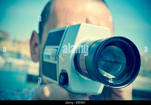 Closeup von einem kaukasischen Jüngling Dreharbeiten mit einem Retro-Film-Kamera im freien Stockbild