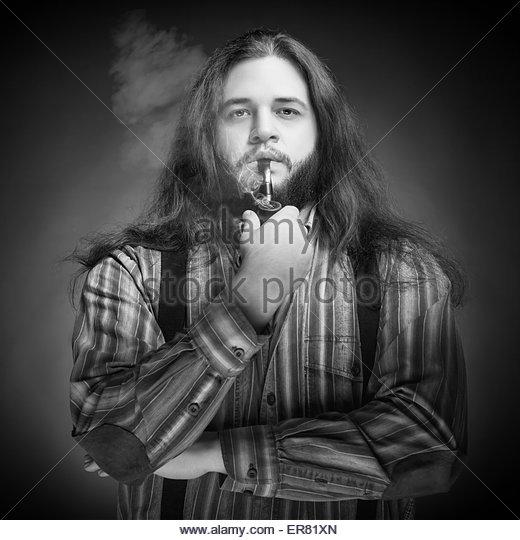 Männer mit langen Haaren raucht Pfeife. Professionelle Studiobeleuchtung. Konzept. Schönheit. Mode Stockbild