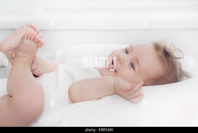 niedliche kleine glückliches Baby junge liegen auf weichen weißen Kissen, glücklich Familienkonzept Stockbild