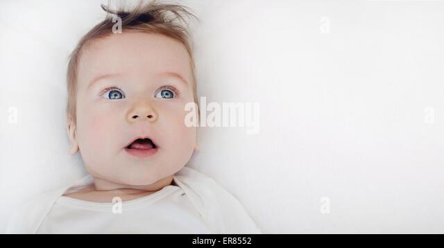 Porträt von niedlichen kleinen glückliches Baby jungen liegen auf weichen weißen Kissen, glücklich Stockbild