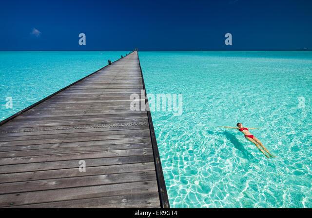 Junge Frau im roten Bikini schwimmen neben Steg im azurblauen Wasser der Malediven Stockbild