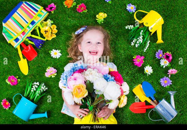 Kinder im Garten. Kinder mit Gartengeräten. Kind mit Gießkanne und Schaufel. Kleines Kind Blumen gießen. Stockbild