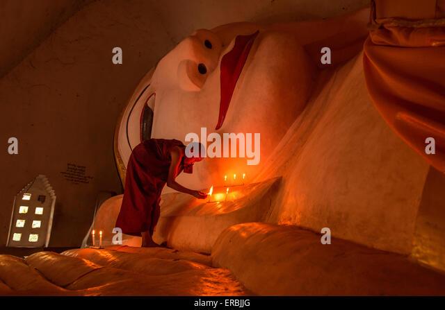Mönch Anzünden von Kerzen am ruhenden Buddha im Mandalay Myanmar Stockbild