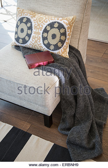 Kissen, Decke und Buch auf Stuhl Stockbild