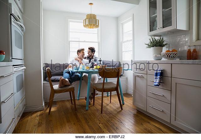 Homosexuelles Paar umarmt am Frühstückstisch Stockbild