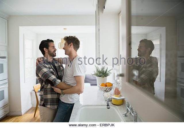Liebevolle homosexuelles Paar umarmt von Angesicht zu Angesicht Küche Stockbild