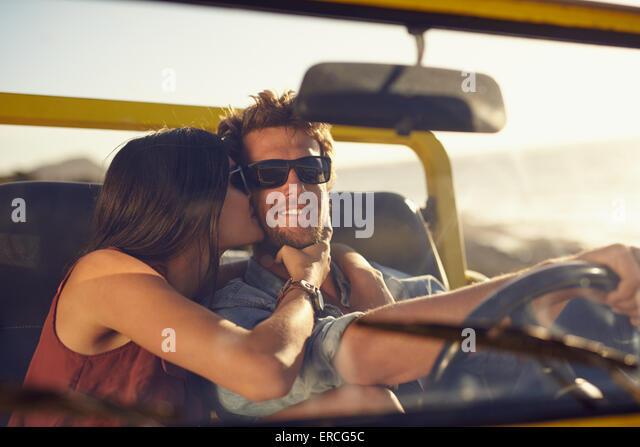 Junges Liebespaar auf Roadtrip. Frau ihres Freundes Wangen küssen. Junger Mann, ein Auto zu fahren. Romantische Stockbild