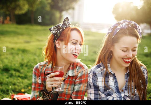 Zwei Mädchen glücklich im Pin-up-Stil auf Picknick, lachen, trinken Wein, Spaß zu haben. Selektiven Stockbild