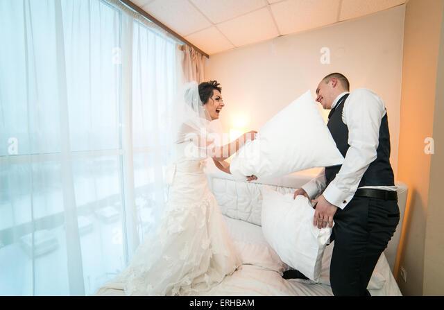 Kissenschlacht von Braut und Bräutigam in einem Hotelzimmer Stockbild